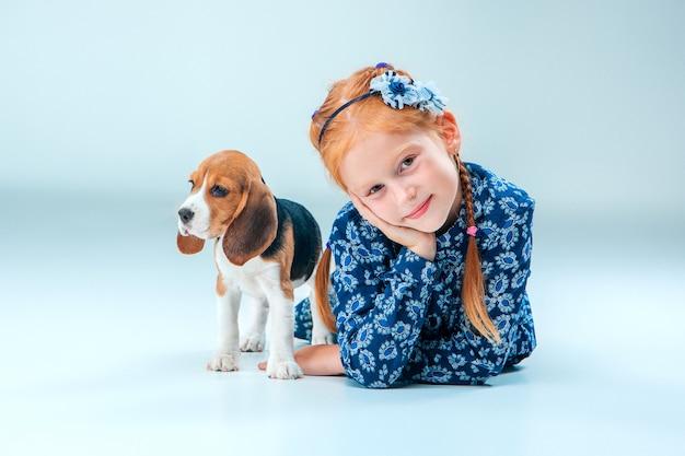 La niña feliz y un cachorro beagle en pared gris Foto gratis
