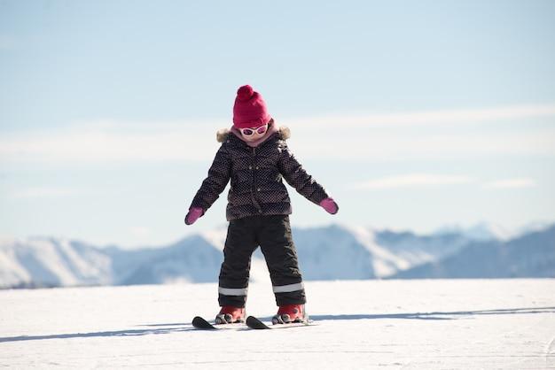 Niña feliz esquiando cuesta abajo Foto Premium