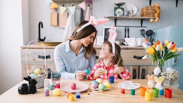 Niña feliz pintando huevos para pascua con madre Foto gratis