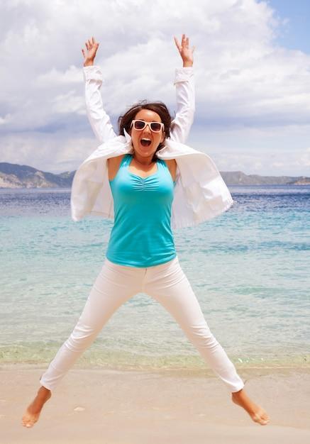 Niña feliz saltando en la playa Foto Premium