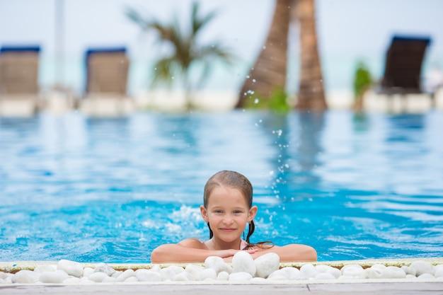 Niña feliz sonriente en la piscina al aire libre Foto Premium