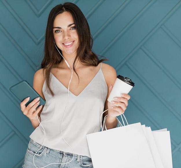 Niña feliz con teléfono inteligente y auriculares Foto gratis