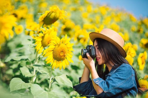 La niña está feliz de tomar fotos en el campo de girasol. Foto gratis