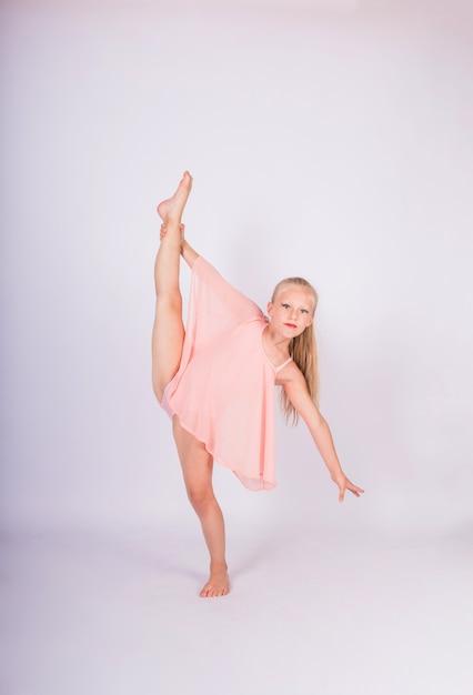 Una niña gimnasta en traje de baño deportivo realiza una pose de gimnasia rítmica en una pared blanca aislada Foto Premium