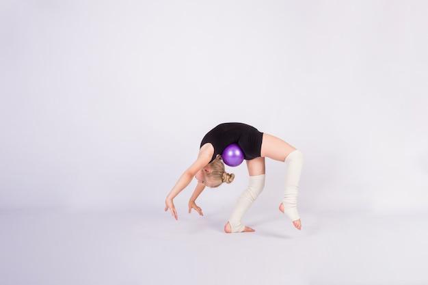 Una niña gimnasta en traje de baño negro hace un ejercicio de puente con una pelota en una pared blanca aislada con espacio para texto Foto Premium