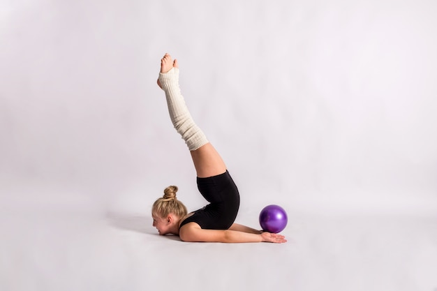 Una niña gimnasta en traje de baño negro realiza un ejercicio gimnástico con una pelota en una pared blanca aislada con espacio para texto Foto Premium