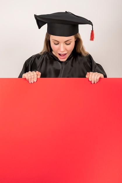Niña graduada sosteniendo cartel rojo maqueta Foto Premium