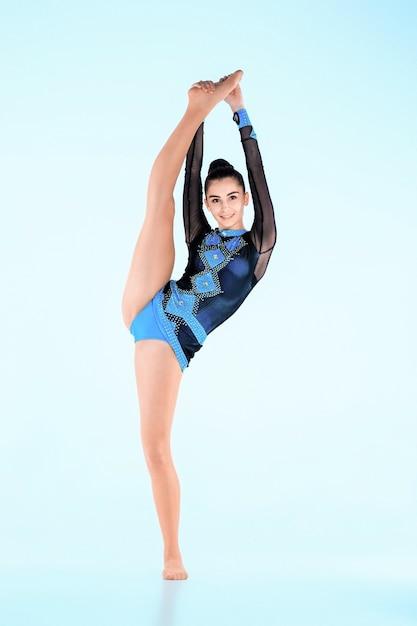 La niña haciendo gimnasia danza en una pared azul Foto gratis