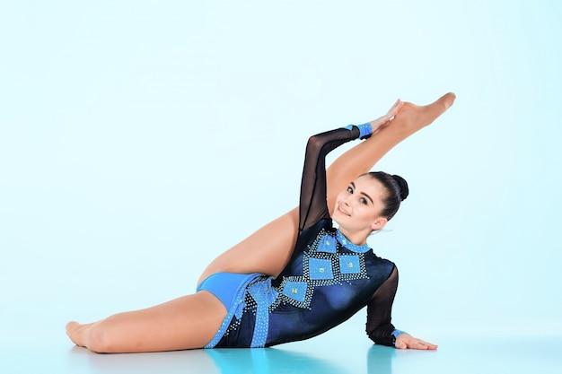 La niña haciendo gimnasia danza sobre un fondo azul. Foto gratis