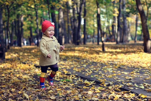 Niña hermosa caminando en el parque otoño Foto Premium