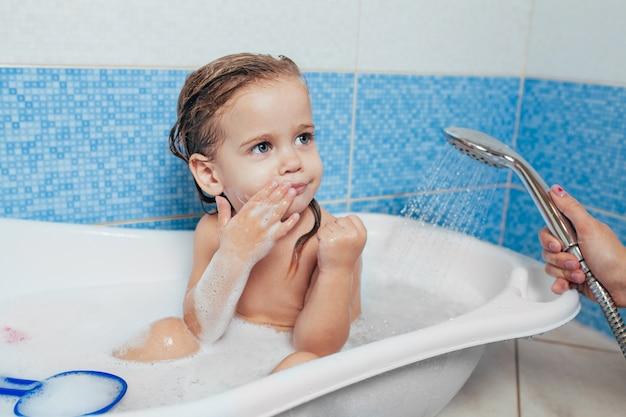 Niña hermosa que toma un baño en casa. Foto Premium