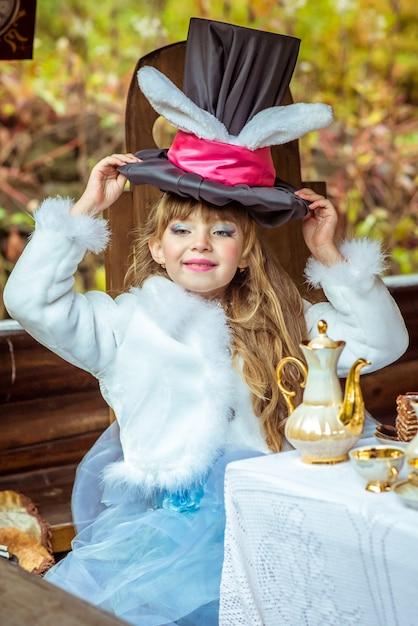 Una niña hermosa con sombrero cilíndrico con orejas como un conejo sobre la cabeza en la mesa Foto Premium