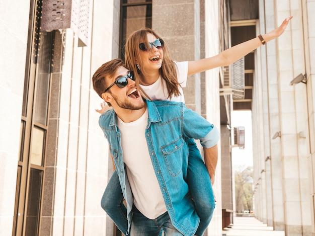 Niña hermosa sonriente y su novio guapo en ropa casual de verano. hombre con su novia en la espalda y ella levantando las manos. Foto gratis