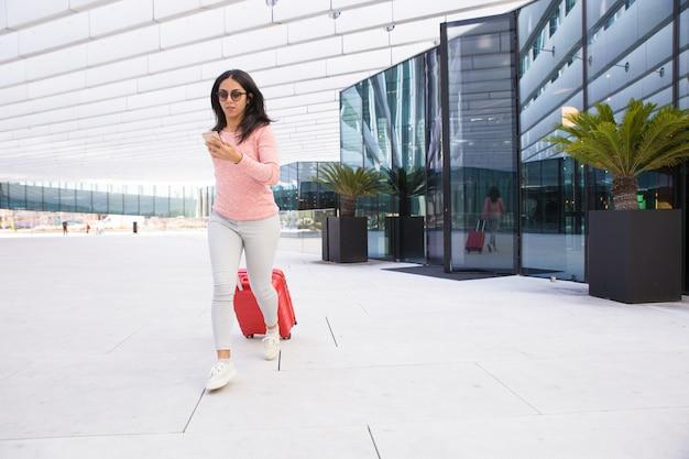 Niña india cargando equipaje con ruedas y corriendo al aeropuerto Foto gratis