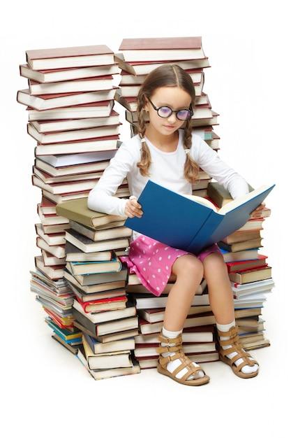 Niña inteligente sentada en muchos libros | Foto Gratis