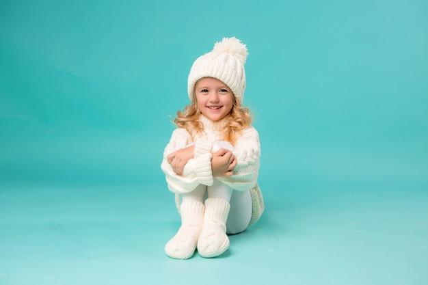 Niña en invierno blanco gorro de punto y suéter en azul Foto Premium