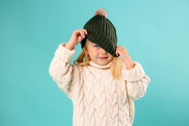Niña en invierno sombrero y suéter en azul Foto Premium