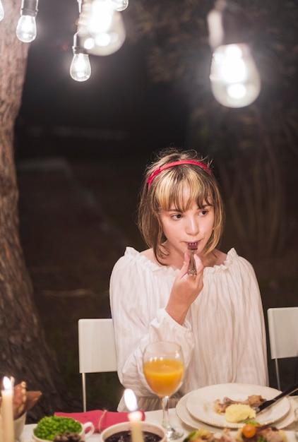 Niña joven, comida, con, tenedor, en, cena de navidad Foto gratis