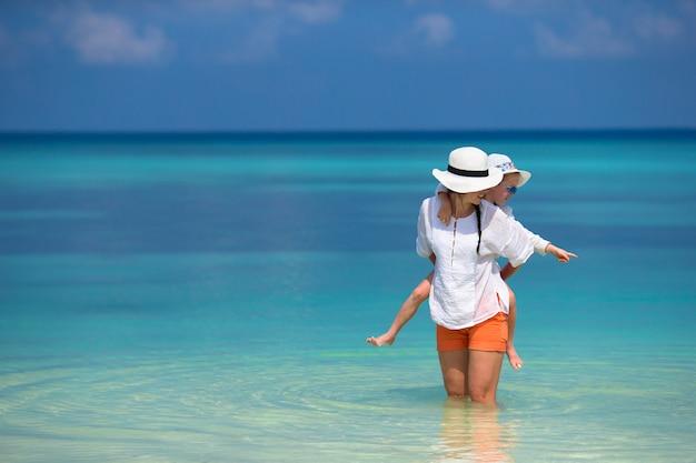 Niña y joven madre durante vacaciones en la playa Foto Premium