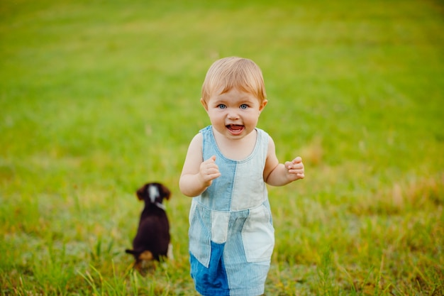 La niña juega con el perrito en el campo Foto gratis
