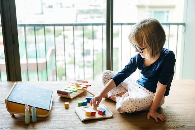 Niña jugando con juguetes de madera Foto Premium