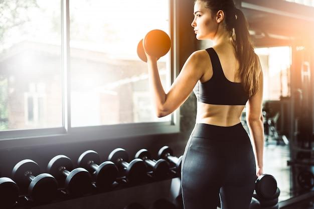 Niña jugando con mancuernas para hacer ejercicio en fitness Foto Premium