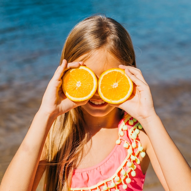 Niña jugando con naranja en la playa Foto gratis