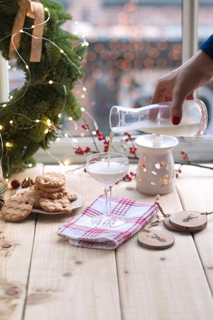 Niña leche en un vaso en la mesa junto a la ventana, galletas en un plato y una corona de árbol de navidad Foto Premium