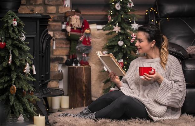 Niña leyendo un libro en un acogedor ambiente hogareño cerca de la chimenea Foto gratis