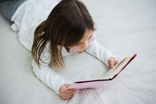 Niña leyendo un libro Foto gratis