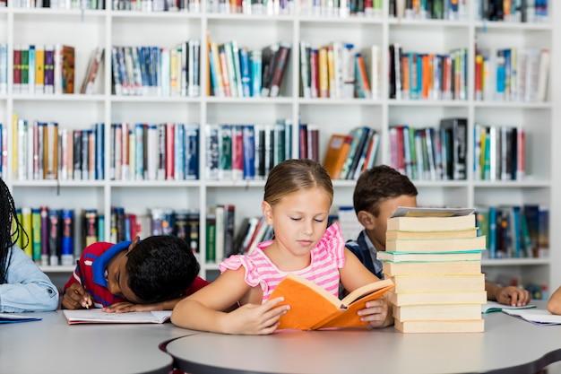 Una niña leyendo libros Foto Premium