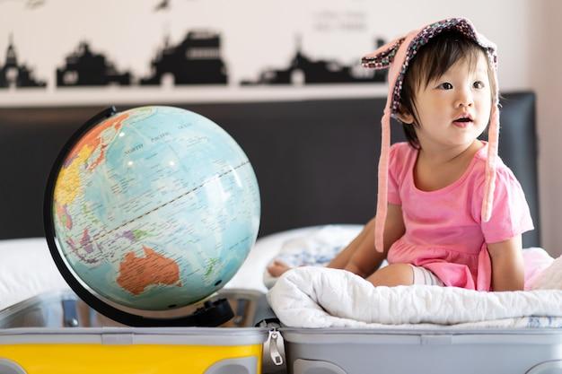 Niña linda asiática con sombrero sentado en una bolsa de viaje con una sonrisa divertida y riendo en la cama en el dormitorio con globo terráqueo puesto en el otro lado de la bolsa de la maleta. Foto Premium