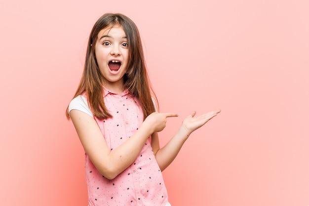 Niña linda emocionada sosteniendo en la palma. Foto Premium