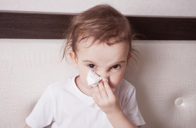 Niña linda enferma que sopla su nariz Foto Premium