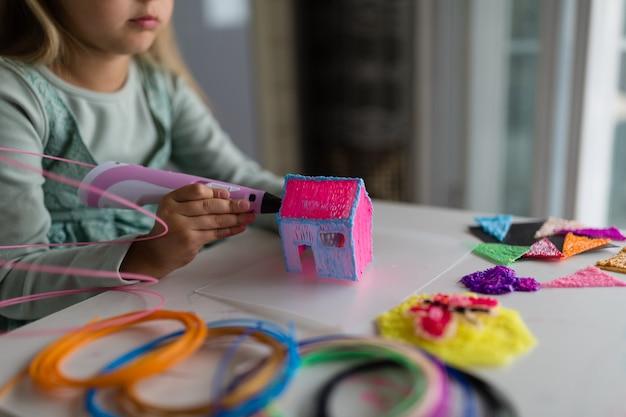 La niña linda hace una casa de plástico, dibuja piezas con un bolígrafo 3d. desarrollo, modelado, educación, diseño con plástico caliente. tecnologías modernas bricolaje. Foto Premium