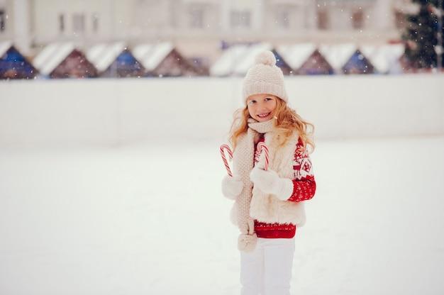 Niña linda y hermosa en una ciudad de invierno Foto gratis