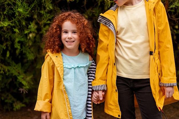 Niña linda y niño hermano en impermeables sonriendo juntos en el bosque Foto Premium