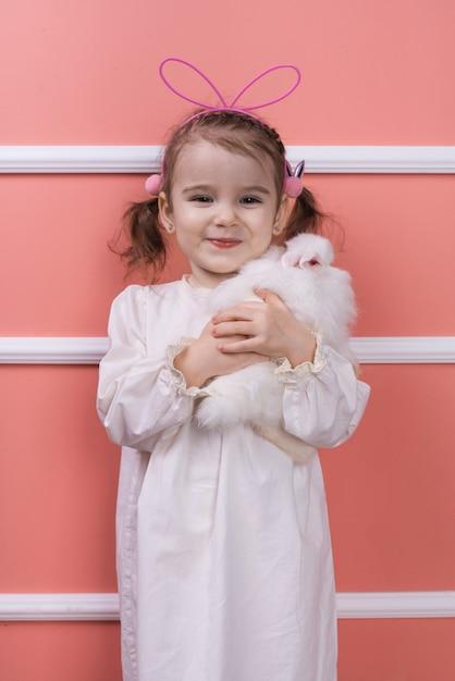 Niña linda en orejas de conejo con conejo Foto gratis