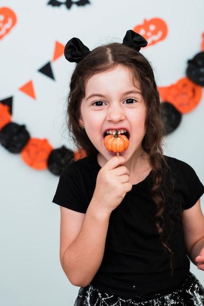 Niña linda que come un caramelo pumpking Foto gratis