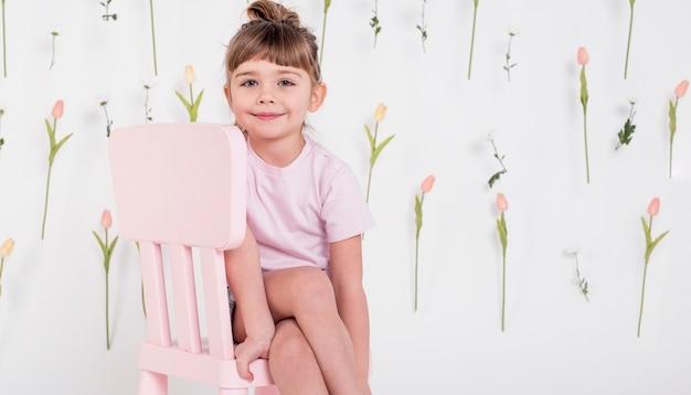 Niña linda que se sienta en silla Foto gratis
