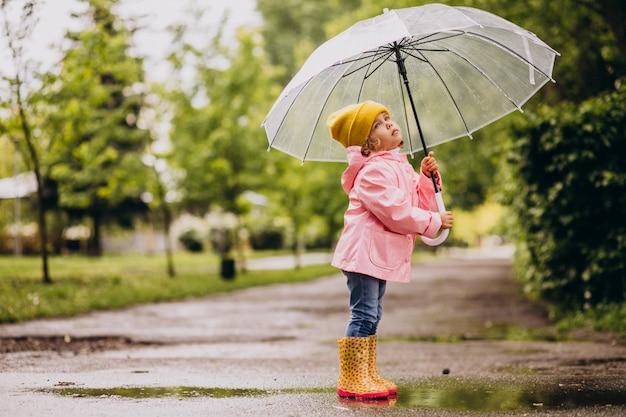 Niña linda saltando en el charco en un clima lluvioso Foto gratis