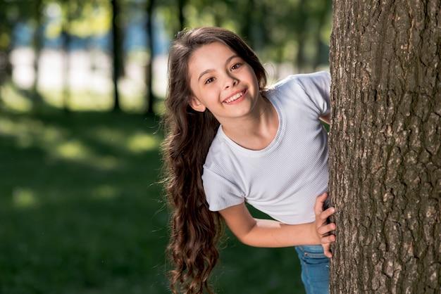 Niña linda sonriente mirando por detrás del tronco del árbol al aire libre Foto gratis