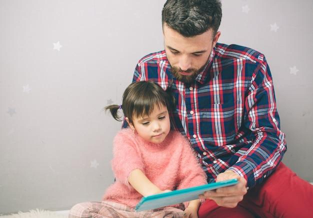 La niña linda y su padre hermoso están usando una tableta digital y están sonriendo, sentándose en casa. Foto Premium