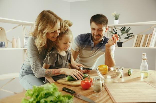 Niña linda y sus hermosos padres están cortando verduras y sonriendo mientras hacen ensalada en la cocina de casa. concepto de estilo de vida familiar Foto gratis