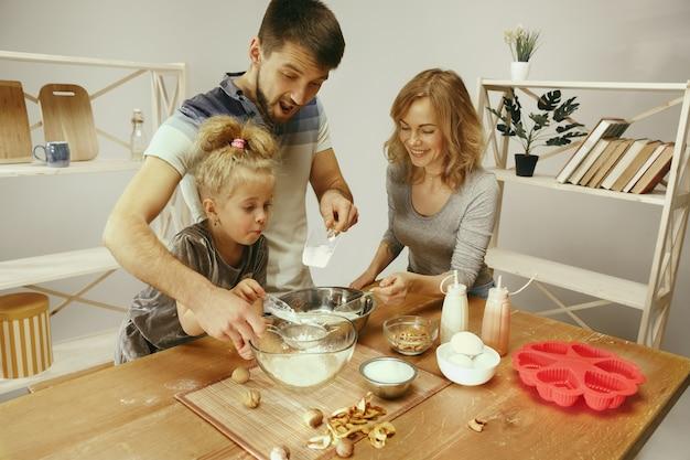 Niña linda y sus hermosos padres preparando la masa para el pastel en la cocina de casa. concepto de estilo de vida familiar Foto gratis