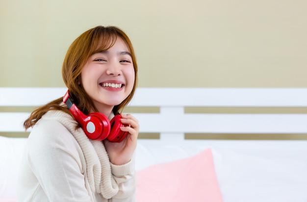 La niña llevaba auriculares y disfrutaba de la música en la cama. Foto gratis