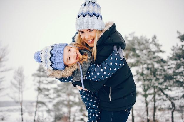Niña con madre jugando en un parque de invierno Foto gratis