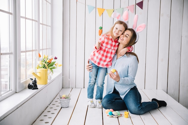 Niña y madre en orejas de conejo sentado con huevos de pascua Foto gratis
