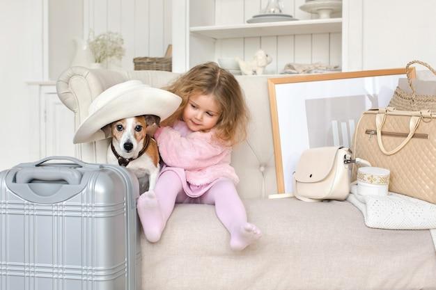 Una niña con maletas y un perro en el interior. Foto Premium
