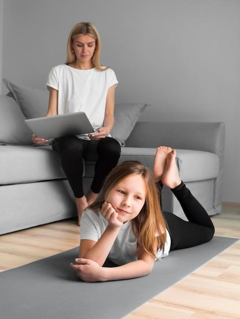 Niña con mamá haciendo deporte en estera Foto gratis